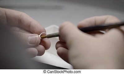 Close up of dental technician hands working on false teeth. ...