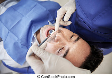 close up of dentist checking male patient teeth