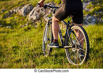Close-up of detail of cyclist man feet riding mountain bike on rocky trail.