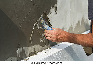 Close-up of detail of worker hand with trowel applying glue on plastered white house wall doing insulation with polyurethane foam. Modern technology, alternative for mineral wool concept.