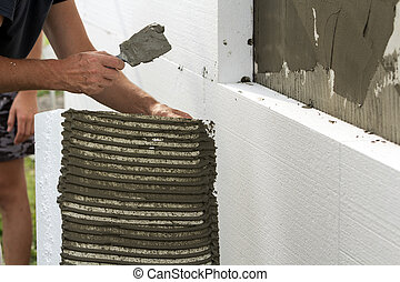 Close-up of detail of worker with trowel gluing white rigid polyurethane foam sheet to house wall Modern technology, insulation, renovation, professional job, alternative for mineral wool concept.