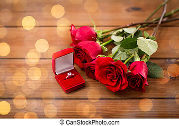 close up of diamond engagement ring and red roses - love,...