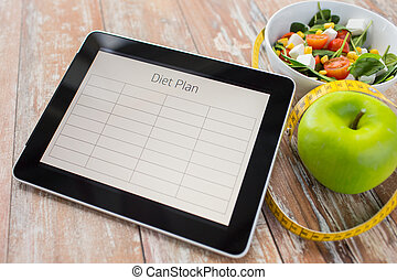 close up of diet plan on tablet pc and food - healthy eating...