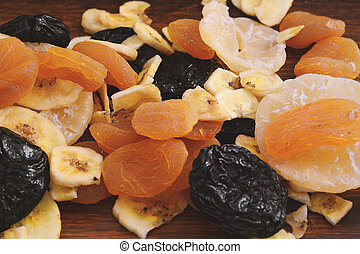 Close up of different dried fruits on wooden background