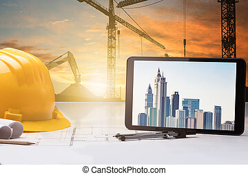 Digital Tablet And Hardhat On Blueprint