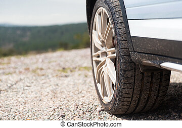 close up of dirty car wheel on cliff - transport, driving...