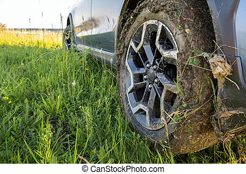 Close up of dirty off road car wheels with dirty tires covered with yellow mud.