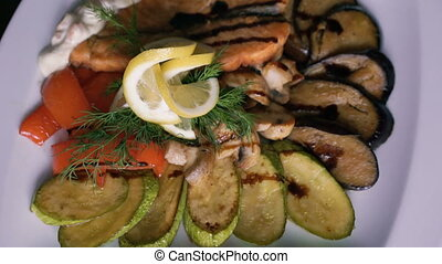 Close up of dish of stewed salmon with vegetables turning around on plate