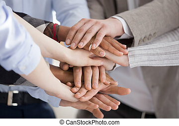 Close up of diverse workers or employees put hands in stack showing support and unity, reach shared goal together, multiracial people engaged in teambuilding activity or training. Teamwork concept