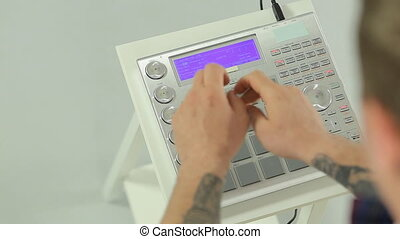 Close up of DJ mixing music on a panel of the midi controller