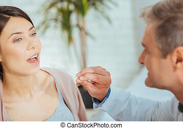 Close up of doctor checking throat of lady