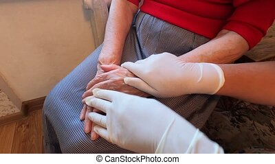 Close up of doctor hands in protective gloves comfortin a stressed old woman sitting on hospital bed in clinic. Global pandemic coronavirus covid-19 healthcare pandemic