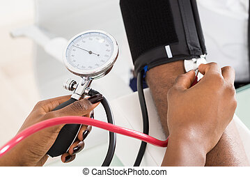 Doctor Measuring Patients Blood Pressure - Close-up Of...