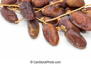 close up of dried dates on white background