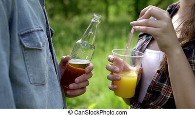 Close-up of drinks in the hands of two friends. Outside