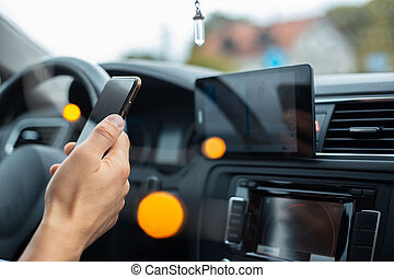 Close-up of driver hand holding smartphone inside car.