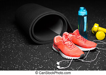 Close-up of dumbbells, sports shoes, bottle for water and phone with handphones on a black floor background. Copy space.