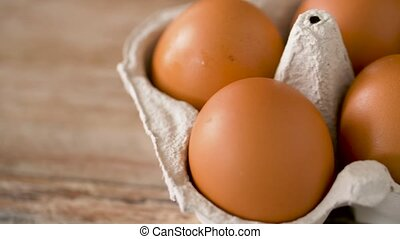 close up of eggs in cardboard box on wooden table - food,...