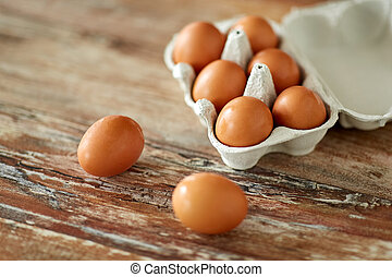 close up of eggs in cardboard box on wooden table