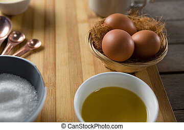 Eggs in wicker basket with oil, and sugar on wooden board