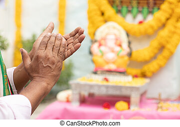 Close up of Elder man hands offering Bhajan or hymn in front of Lord Ganesha Idol by clapping during Ganesha or vinayaka Chaturthi festvial ceremony at home
