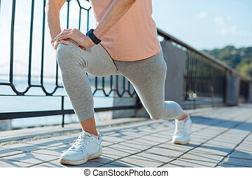 Close up of elderly woman doing lunges before jogging