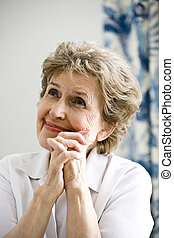 Close up of elderly woman thinking happy thoughts