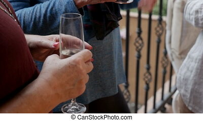 Close up of elderly women's hands holding drinks and glasses