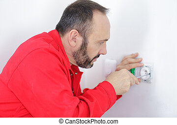 close up of electrician hands fixing a socket
