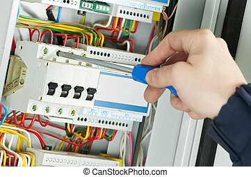 Close-up of electrician work on a industrial panel mounting and assembling new wiring