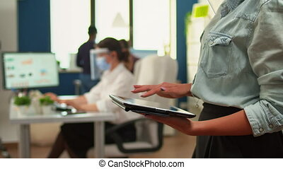 Employee using tablet standing in office room while team of financial analysts working in background. Multiethnic coworkers respecting social distance in business company during coronavirus pandemic.
