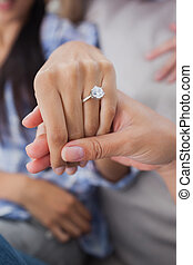 Close up of engagement ring on womans hand held by friends ...