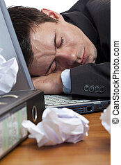 Close-up of exhausted, tired businessman sleeping at desk. ...