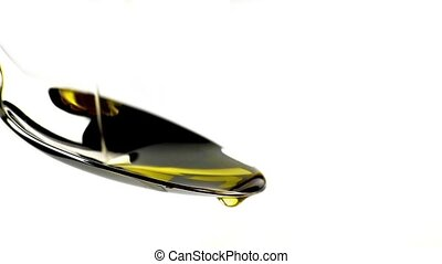 close-up of extra virgin olive oil over a spoon with drops isolated on white background, nutrition concept