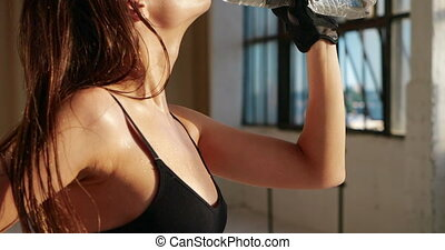 Close-up of face and bust beautiful pretty caucasian woman with makeup quenching thirst with pleasure drinking water in bottle in heat after workout in isolated white gym opposite sun outside window