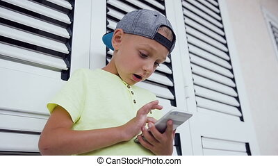 Close up of face and hands of 5-6 years old boy playing computer games standing near white window in outdoor. Kid using telephone. Concept of teen and technology