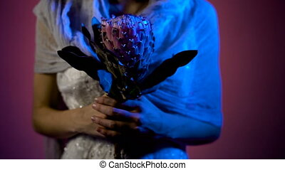 Close up of face of a young girl standing with the pink flower in her hands and her face with art paiting in Halloween theme. Phantom of young girl is standing in the dark room in white wedding dress