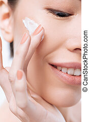 Close up of facial cream being applied on the cheek