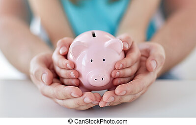 close up of family hands with piggy bank - family, children...