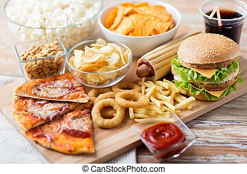 close up of fast food snacks and drink on table - fast food...