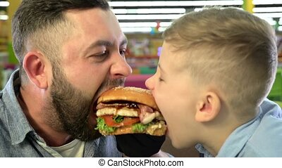 Close-up of father and son eating burger at restaurant. -...