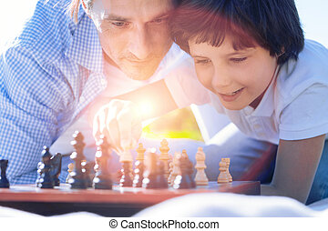 Close up of father and son playing chess