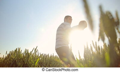 Close-up of father and son playing together. on the wheat field. Young father rotates his son in hands