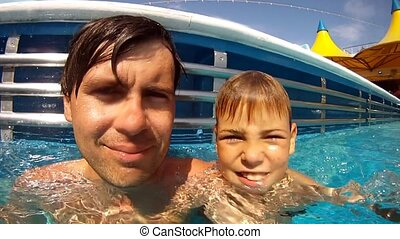 Close-up of father and son, which swim in swimming pool
