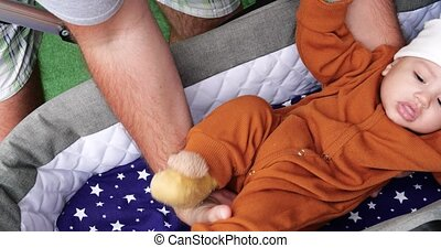 Close-up of father hands, lovingly put her cute little baby in a stroller