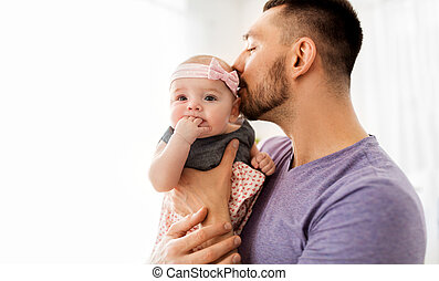 close up of father kissing little baby daughter