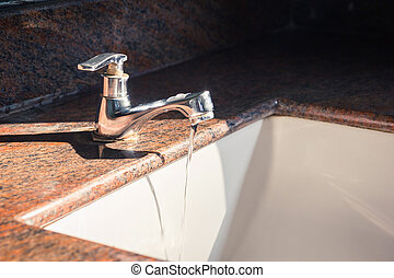Close up of faucet and water flow on basin