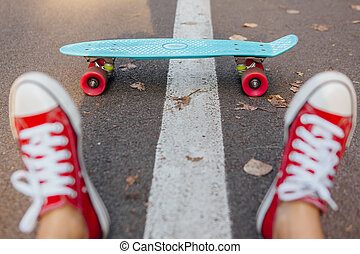 Close up of feet and blue penny skate board with pink wheels.