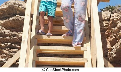 Close-up of feet descending a steep wooden staircase to the sea, view from the bottom