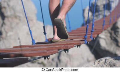 Close up of feet extreme man is walking on the rope on long...